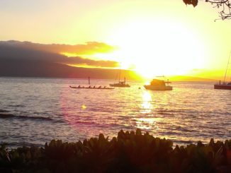 A 6 person outrigger canoe paddles past moored sailboats. The sunsets in the background.