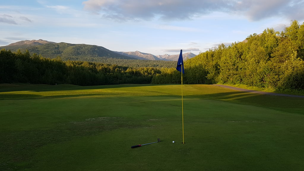 photo of a flagstick, with fairway and mountains in the background.